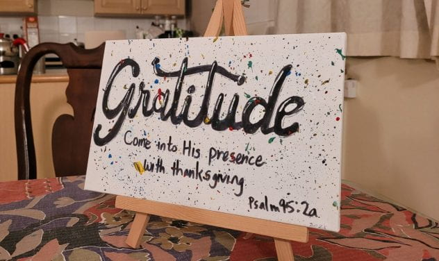 One word for 2021 --gratitude written on a canvas setting on a small easel
