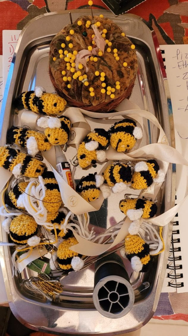 Crocheted bees on a tray in various stages of being completed, along with some pins and needles and thread..