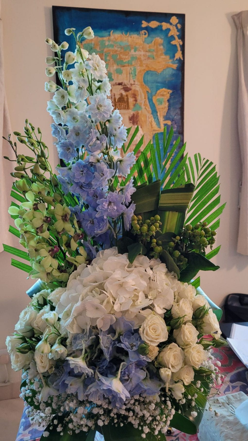 bouquet of flowers in a vase with a painted map of Bahrain behind them